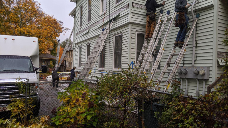 Blow in cellulose being installed in a multifamily building for energy efficiency. Seven ladders on buildings with four crew members.