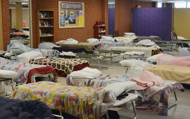 A representative temporary shelter with cots, but with donated blankets and quilts. The average stay in shelter in MA is ten months. Insurance Against Homelessness promises to shorten this average stay by 45 days at least. (CC-BY KOMU News Missouri)